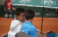 Novak Djokovic shares his umbrella with a ball boy during a French Open rain delay