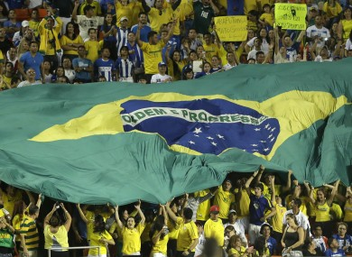 A large Brazilian flag is passed along by fans at a friendly football match in 2013.