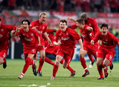 Liverpool players running to goalkeeper Jerzy Dudek to celebrate after AC Milan's Andriy Shevchenko missed his penalty.