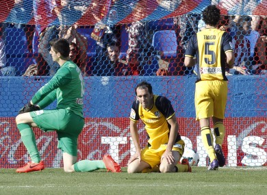 Atletico de Madrid's goalkeeper Thibaut Courtois from Belgium, left, and Diego Godin from Uruguay, center, stay on the ground after Levante scored their second goal.