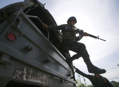A Thai soldier jumps off a military truck after arriving at a pro-government rally site on the outskirts of Bangkok.