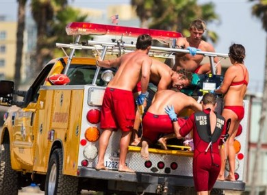 Lifeguards assist a person who was in the water and apparently struck by lightning.