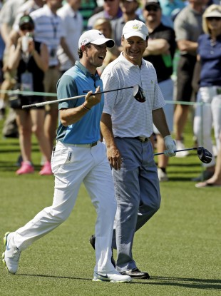 Rory McIlroy walks with Jeff Knox down the eighth fairway at Augusta last year.