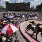 A circus performer dressed in native American garb leaps on and off a running horse, during a free public show to protest Mexico City's ban on circus animals in Mexico City's main square, the Zocalo. Photographed by: Rebecca Blackwell