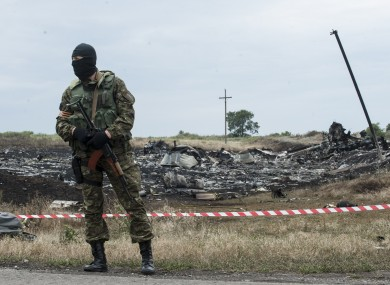 A pro-Russian fighter guards the crash site.