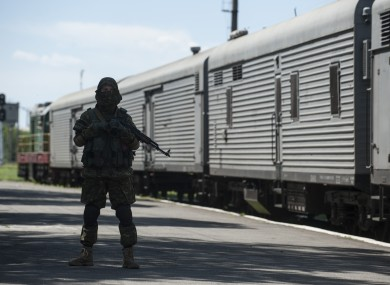 A pro-Russia fighter guards the platform in Torez, eastern Ukraine, as the train bearing bodies of MH17 victims leaves the station.