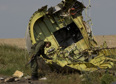 A pro-Russian rebel touches the MH17 wreckage at the crash site of Malaysia Airlines Flight 17, near the village of Hrabove, eastern Ukraine.
