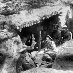 German soldiers of the 12th (2nd Brandenburg) Regiment playing cards in a dugout in a shallow trench in German-occupied Russian Poland during the First World War. One of the soldiers (far right) is holding an accordion.<span class=
