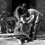 A French Aid Station in 1914. An injured soldier is tended to by French Army medical orderlies. The motorcycle by the wall is a British-made 1914 Rudge Multi.<span class=