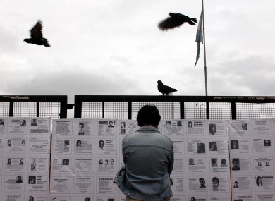 A man looks at pictures of people who disappeared during the dictatorship in Argentina.