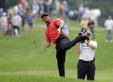 Woods has an awkward follow through after hitting from the lip of a fairway bunker on the second hole.