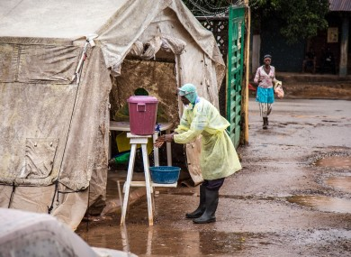 A health worker cleans his hands before entering an Ebola screening tent in Sierra Leone