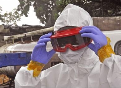 A Liberian health worker prepare his Ebola protective gear.