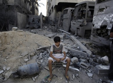 A Palestinian boy sits on rubble following air strikes in Gaza on Wednesay.