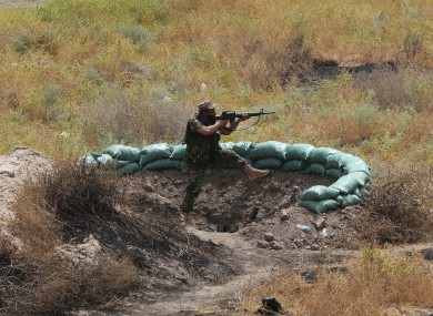 An Iraq Shiite fighter fires his weapon during clashes with militants from the extremist Islamic State group in Jurf al-Sakhar, 43 miles (70 kilometers) south of Baghdad, Iraq, Monday, Aug 18, 2014.