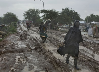 Photo dated July 24, 2014: People trudge along the main passageway through the UN's Malakal Camp for Internally Displaced People during the wet season.