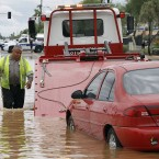 Steven Martinez of Western Towing prepares to lift a vehicle stranded in about two feet of water in Phoenix. <span class=