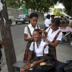 A high school student gets her hair adjusted by friends outside a school Port-au-Prince, Haiti.<span class=