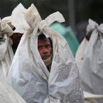Migrant workers cover themselves with plastic sheets to shield from the rain, as they camp on a highway after the area they were living in was inundated by floodwaters in Srinagar, India<span class=