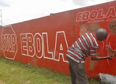 A Liberian artist draws a mural that reads 'Stop Ebola'