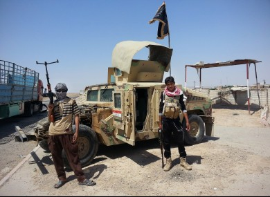 Militants stand with captured Iraqi Army Humvee at a checkpoint outside Beiji refiner in June.