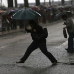 A woman jumps over a puddle as commuters, background, queue to board buses during a partial strike by Lisbon's subway workers.<span class=