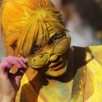 A woman, covered in coloured powder poses, during the Holi Festival of Colours, in Lisbon.<span class=