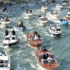 The boat carrying George Clooney and his wife Amal Alamuddin is surrounded by media and security boats as they cruise the Grand Canal after leaving the Aman luxury Hotel in Venice, Italy.<span class=