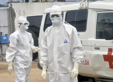 Health workers wearing protective gear wait to carry the body of a person suspected to have died from Ebola, in Monrovia, Liberia.