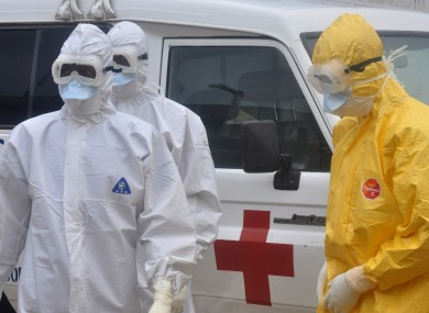Health workers in protective gear wait to carry a body of a person suspected to have died from Ebola in Liberia.