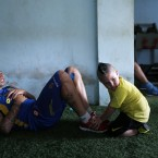 Deportivo Capiata soccer player Fabio Escobar gets a helping hand from his three-year-old son Junior during a training session in Capiata, Paraguay. Capiata has a tiny fan base, and everything about the club is modest: its dressing room, workout room and stadium amenities. (AP Photo/Jorge Saenz)<span class=