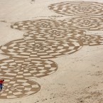 Sand artist Ross Andrews at work on a piece entitled 'Legacy No.II' on Ramsgate beach in Kent, Andrews who grew up in Kent, uses the coast of Thanet as his canvas for artworks produced in about four hours in a race against the tides, he uses a rake and a stick to create his freestyle designs, which he says he does not plan before he starts.<span class=