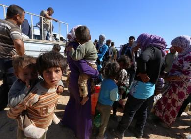 Syrian Kurdish wait for transport as thousands of new Syrian refugees from Kobani arrive at the Turkey-Syria border crossing of Yumurtalik