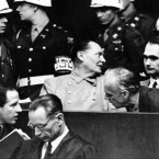 Nazi German Foreign Minister Joachim von Ribbentrop, right, leans in front of Rudolf Hess, Hitler's deputy, to confer with his lawyer, lower left, while Hermann Goering, center, chief of the German air force and one of Hitler's clostest aides, turns to talks with Karl Doenitz, rear right, during the Nueremberg war crime trial.<span class=