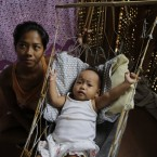 Survivor Emily Sagalis sits next to her baby Bea Joy inside her home at a coastal village in Tacloban.<span class=