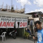 A resident walks past a sign thanking foreign and local donors in the rehabilitation of typhoon-ravaged Basey township.<span class=
