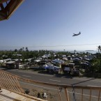 A Philippine Air Force plane flies above a village which was almost totally-wiped out by typhoon Haiyan last year as it prepares to land at Tacloban airport.<span class=