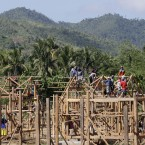 Workers build houses for typhoon survivors at a Government relocation site.<span class=