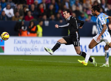 Real Madrid's Gareth Bale, left, scores against Malaga's CF Marcos Alberto Angeleri.