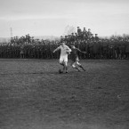 Two players tackle for the ball as soldiers scramble to get a view on the Italian Front, Trissino, Italy.<span class=