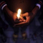 An Indian child holds a candle during a candlelight vigil in memory of the victims the Taliban attack in Peshawar, in New Delhi, India.<span class=