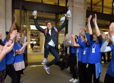 A teenager celebrates after buying a new iPhone at the Apple shop in London