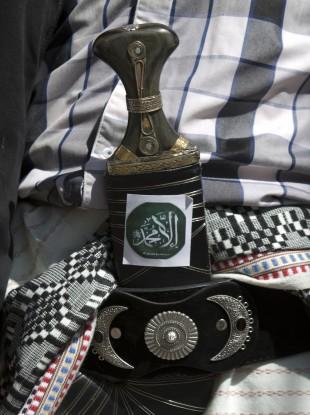 A Yemeni man pastes a sticker on his traditional al-Janbiah dagger. (File photo)