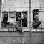 Prisoners look out from behind a barbed wire enclosure. <span class=