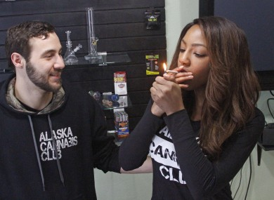 Peter Lomonaco (L) and Charlo Greene of the Alaska Cannabis Club light a joint in Anchorage.