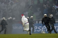Cologne pitch invaders wearing boiler suits clash with police and rival fans in Rhine derby