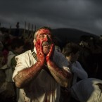 A man covers his face with animal blood to takes part in the ''Momotxorro Carnival'', in Alsasua, northern Spain. Momotxorro, characters who seem to have been resurrected from a prehistoric ritual, come out onto the town's streets. Wearing horns and hiding their faces under headscarves, they are dressed in a white sheet stained with blood, sheepskin gilets, blue trousers, white socks and black sandals. They tour the town roaring fiercely and brandishing their wooden staves, goading and frightening everyone who gets in their way. (AP Photo/Alvaro Barrientos)<span class=