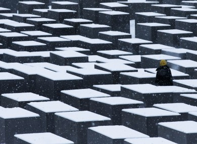 A woman visits the snow-covered Holocaust Memorial in Berlin