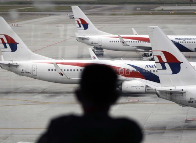 A man views a fleet of Malaysia Airline planes on the tarmac of the Kuala Lumpur International Airport.