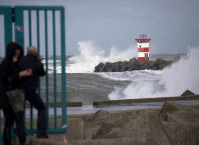 People take pictures of the waves ceasing into a storm barrier and a lighthouse during stormy weather at the entrance to the port of Scheveningen, near The Hague, Netherlands.